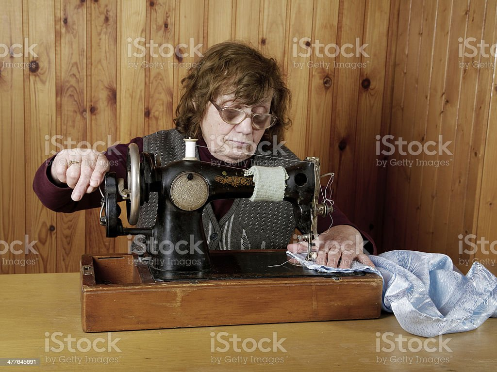 old woman sews on the sewing machine royalty-free stock photo