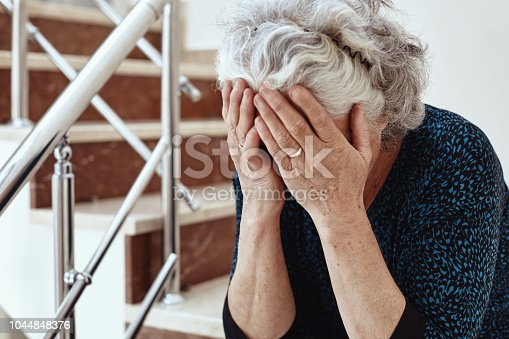 Old woman sitting on steps and crying