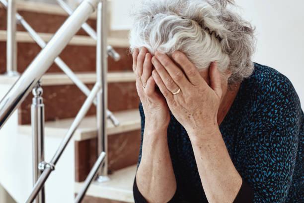 vieille femme assise sur les marches et les pleurs - seulement des femmes seniors photos et images de collection