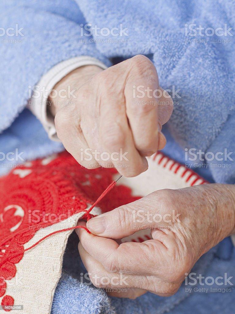 Vecchia donna seduta sul letto e cuciture. qualcosa foto stock royalty-free