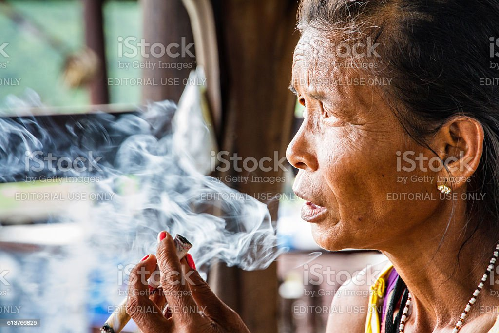 old woman sitting on the street smoking a cigarette stock photo