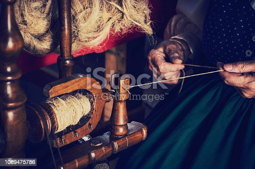 The old woman spinning wool using a traditional spinning wheel. She is wearing a traditional costume.