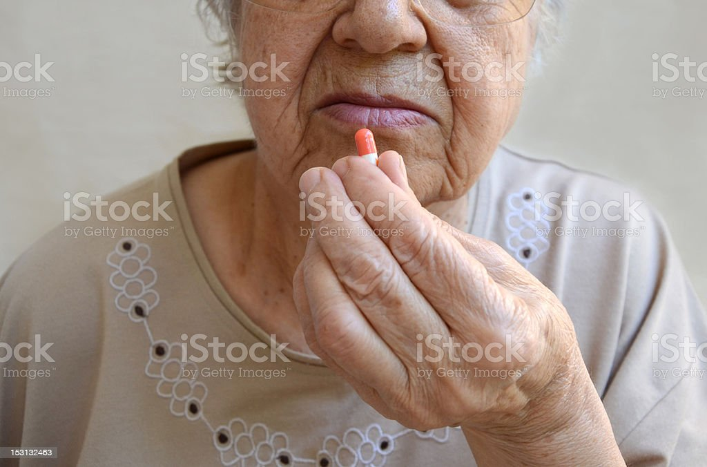 old woman takes the pill stock photo