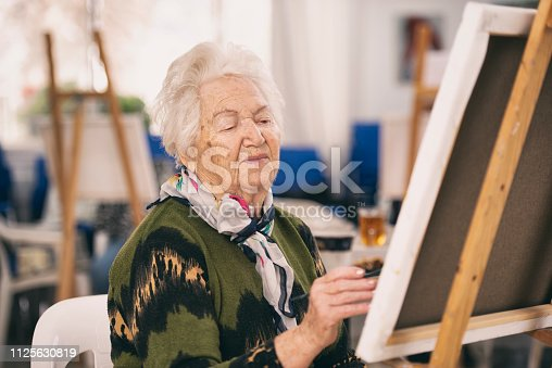 istock Old woman taking an art class. 1125630819