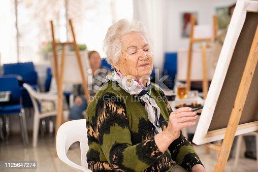 585509074 istock photo Old woman taking an art class. 1125647274