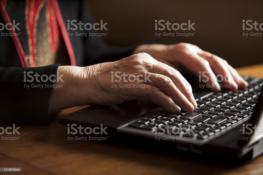 Old woman typing royalty-free stock photo