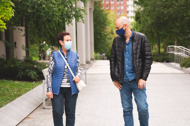 Old woman walking with her son wearing face mask and keeping social distance stock photo