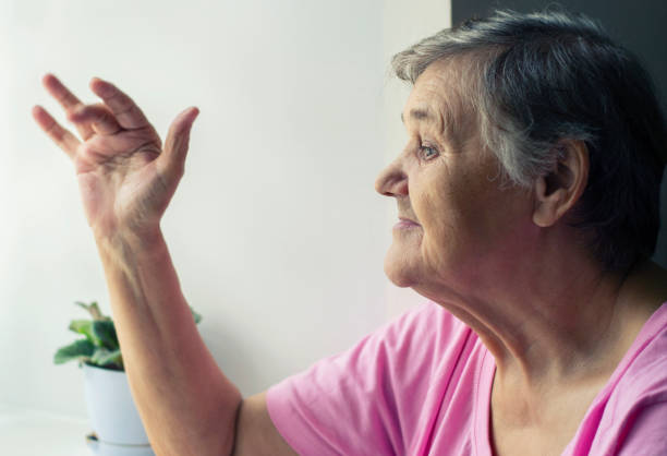 Old woman waving at the window. An elderly woman looks out the window. Portrait of senior woman looking out the window. stock photo