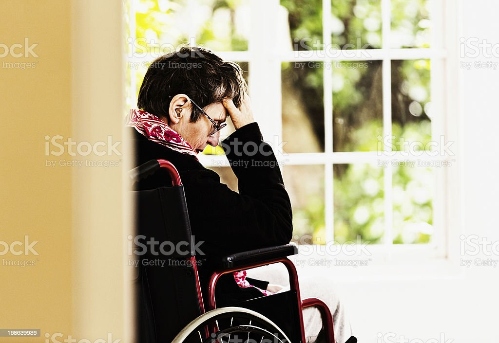Old woman, wheelchair bound with head in hands, is depressed royalty-free stock photo