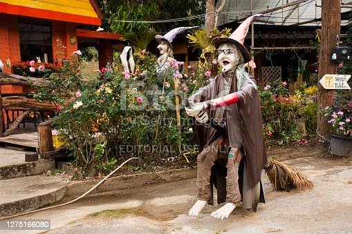 istock Old woman witch figurine and haunted house 1275166080