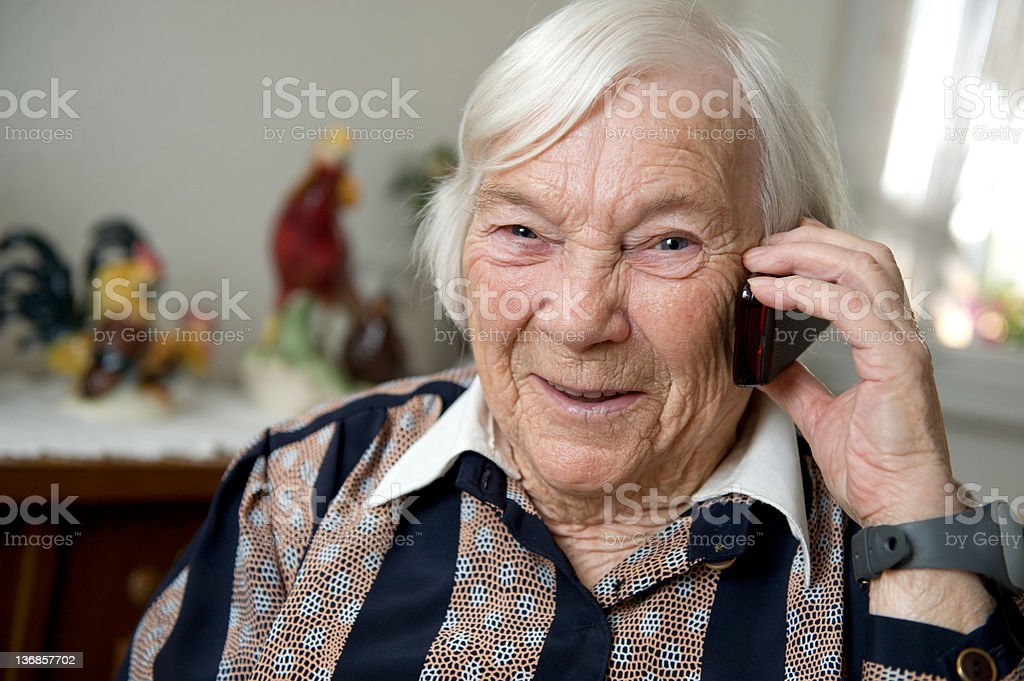 Old woman with a mobile phone at home stock photo