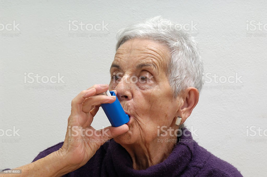 old woman with an inhaler stock photo