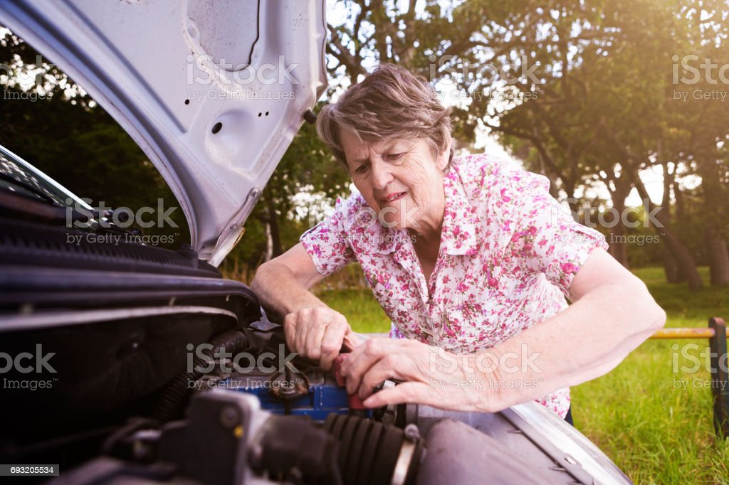 Old woman with broken down car desperately tries to fix it stock photo