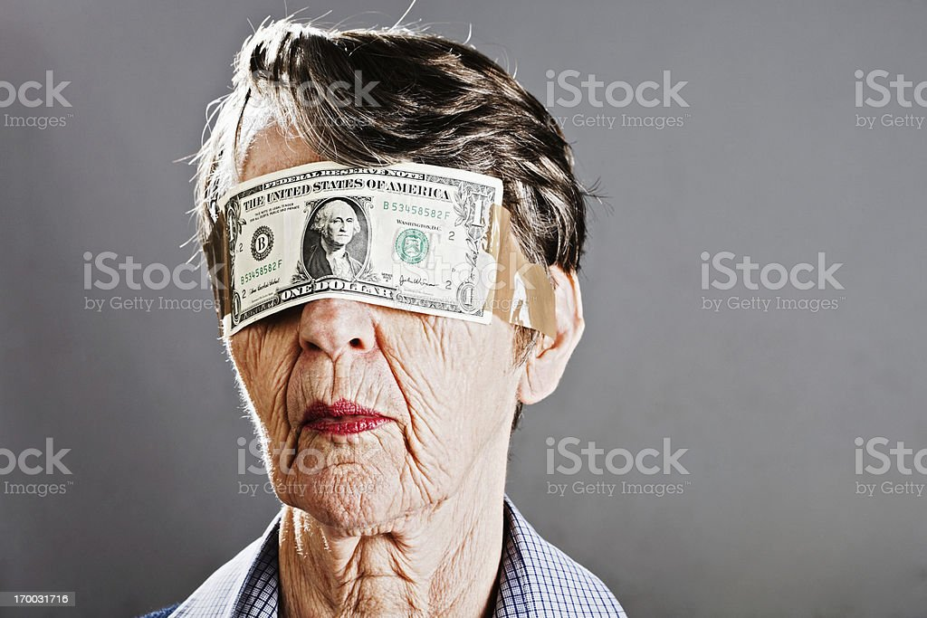 Old woman with dollar blindfold is kept in the dark stock photo