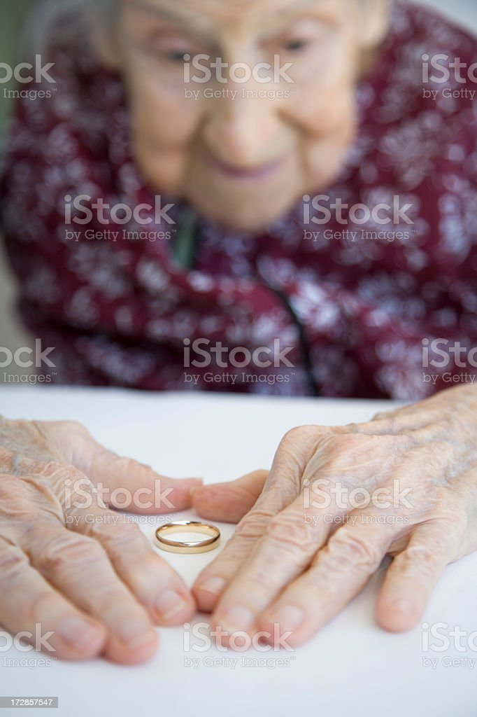 Old woman with hands around wedding band reminiscing royalty-free stock photo
