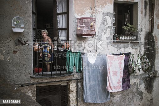 istock Old woman with laundry hung up to dry outide her flat, looking out of a window in the ancient town of Cagliari, Sardinia, Italy. 838198884