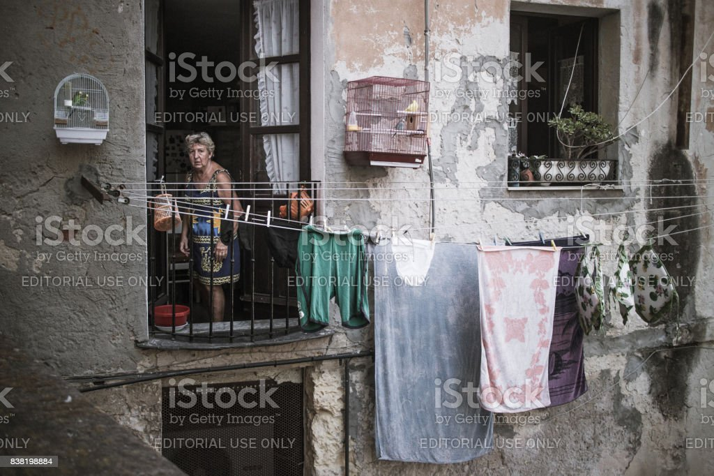 Old woman with laundry hung up to dry outide her flat, looking out of a window in the ancient town of Cagliari, Sardinia, Italy. stock photo