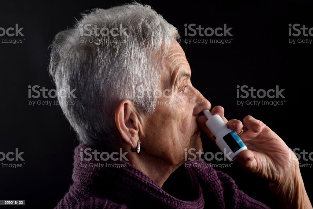 Old woman with nasal spray stock photo