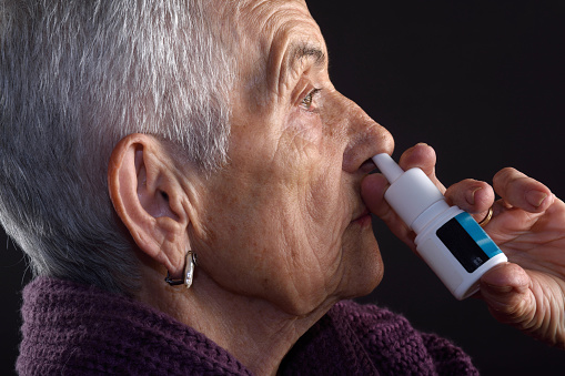 Old woman with nasal spray