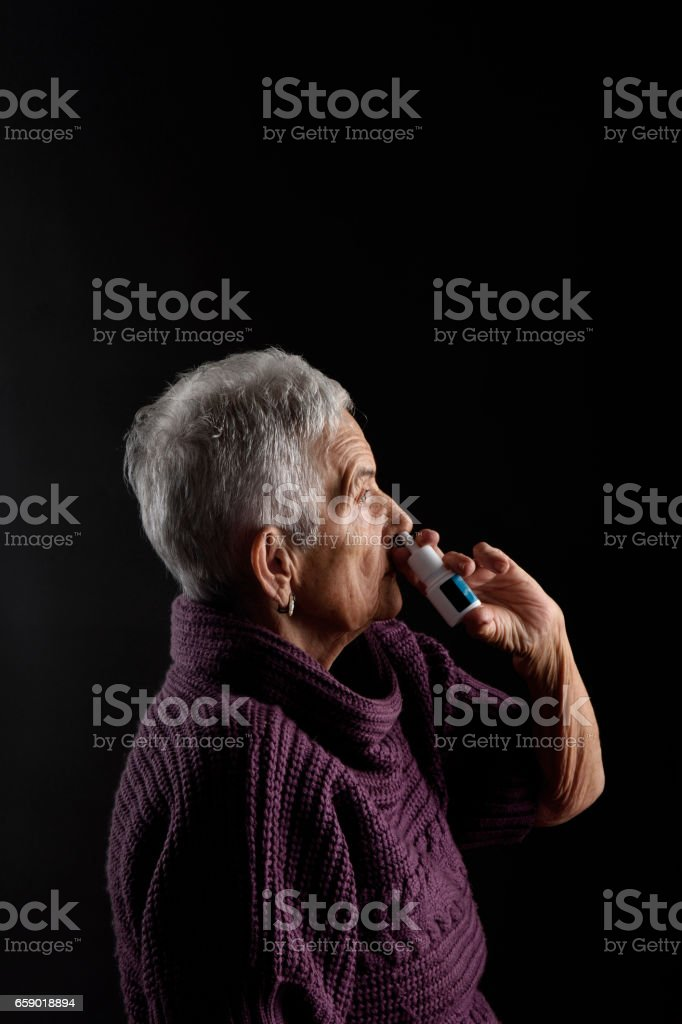 Old woman with nasal spray royalty-free stock photo