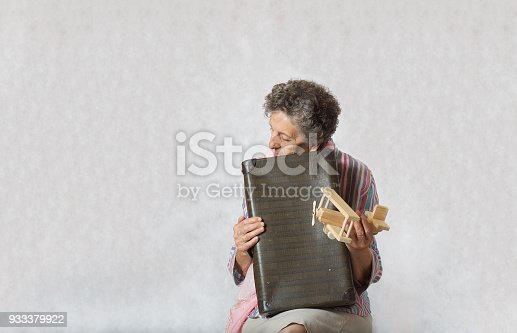 Old woman between 70 and 80 years old with pink scarf and vintage suitcase