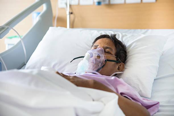 old woman with ventilator mask on hospital bed - ventilator bed stockfoto's en -beelden