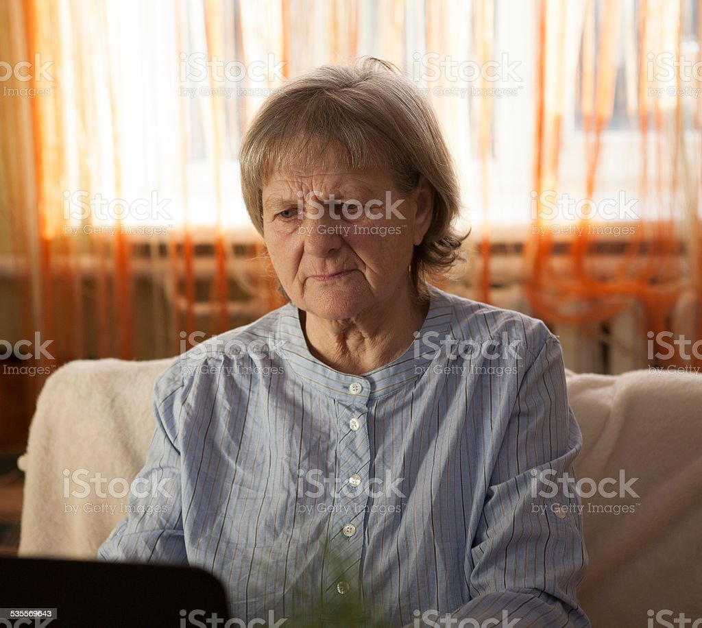 Old woman working on laptop computer at home stock photo