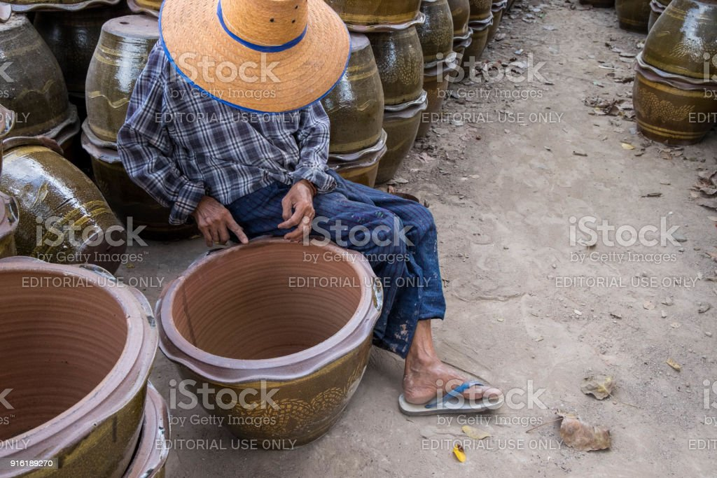 Old woman working on pottery fixing career as routine for her life. stock photo