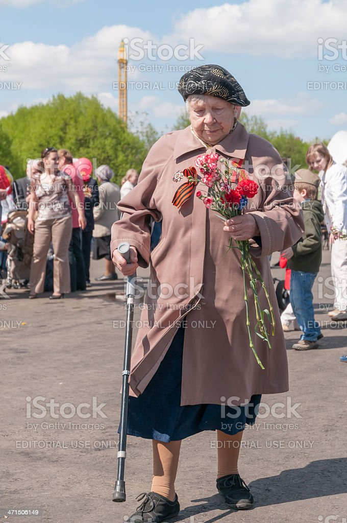 Old woman WWII veteran with walkingstick and bunch walks royalty-free stock photo