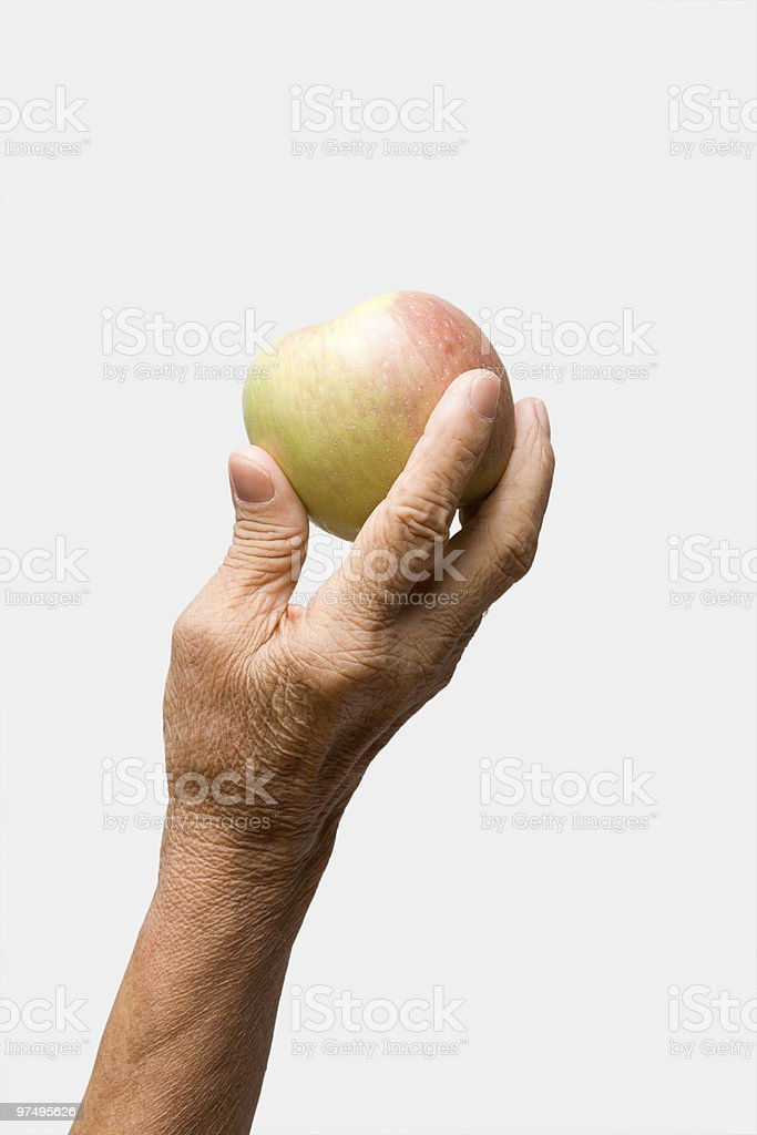 Old woman's hand holding an apple royalty-free stock photo