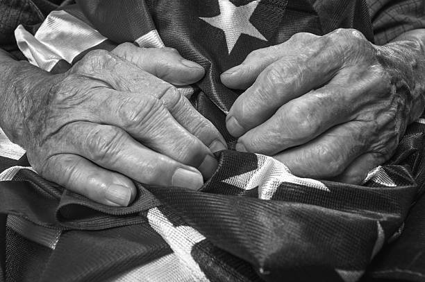 Old woman's hands holding an American flag. Old woman's hands holding an American flag. Black and white image. Selective focus. family 4th of july photos stock pictures, royalty-free photos & images