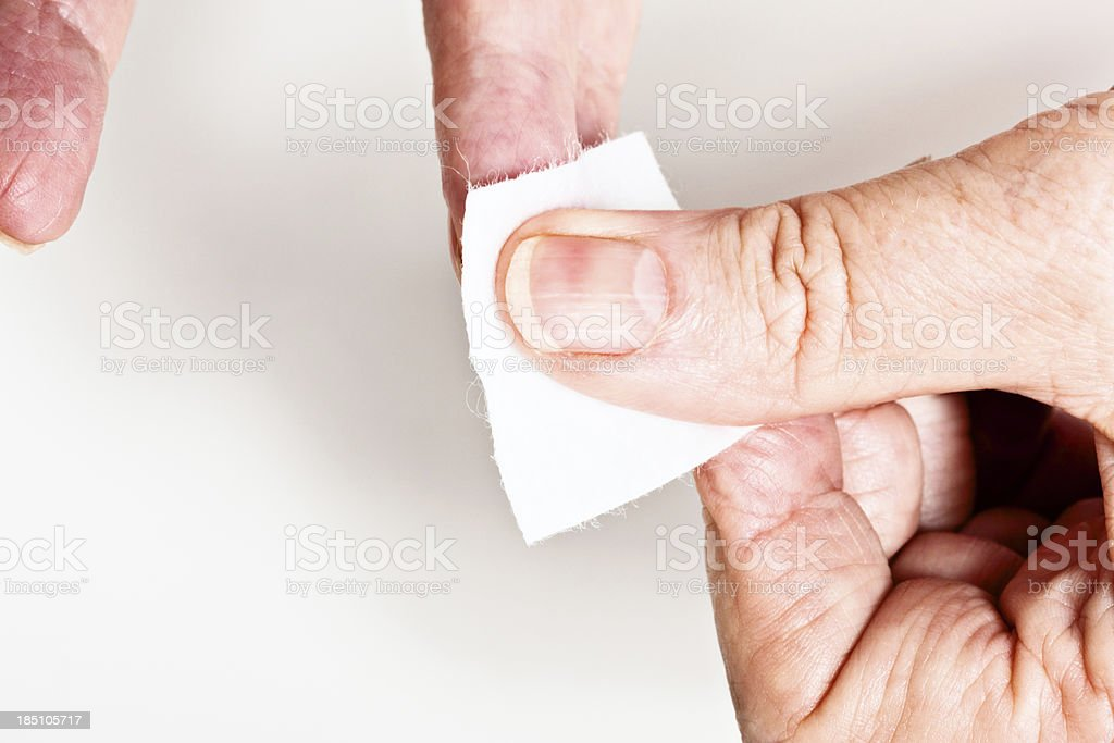 Old woman's hands use sterile swab to wipe finger stock photo