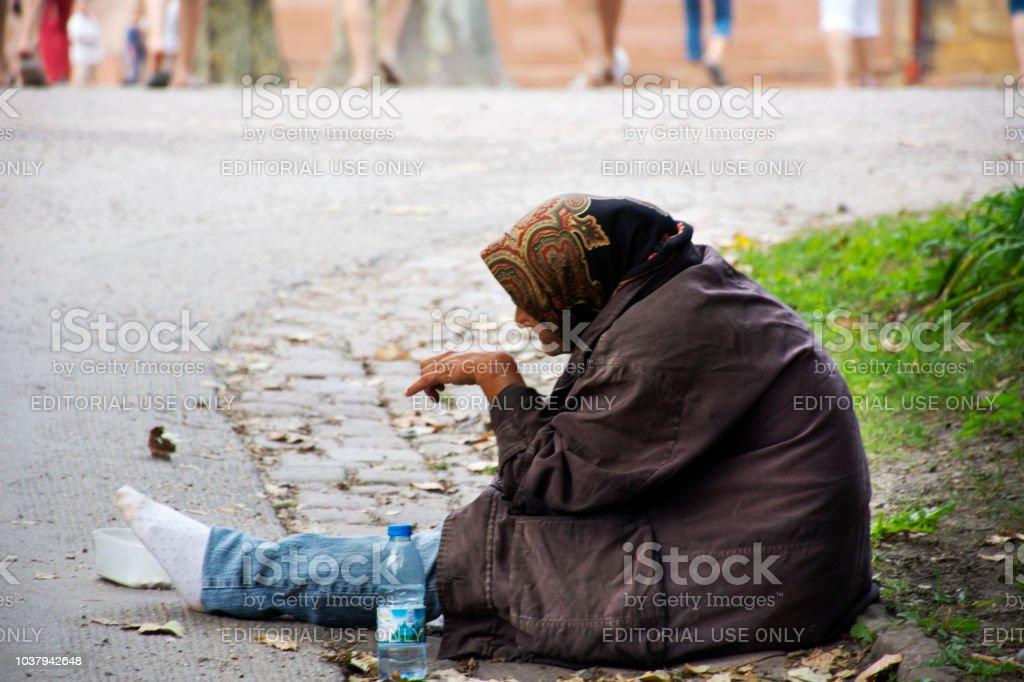 孤独な人々 からお金を物乞いのため経路で座っている老婦人乞食 ...