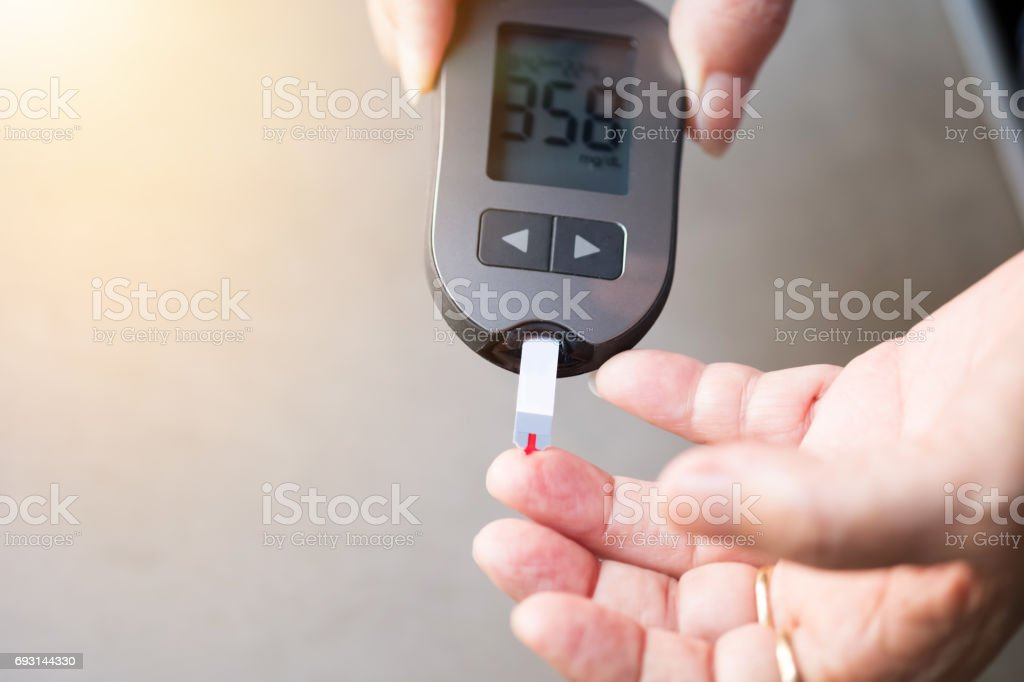 old women checks the amount of sugar in the blood. High blood sugar lever. stock photo