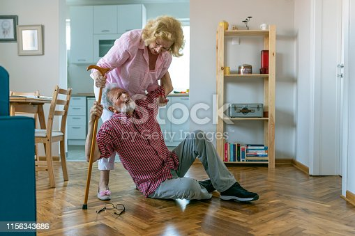 retired woman coming to upset senior husband  sitting on floor with walking cane.senior women helping at old woman who falled down on floor