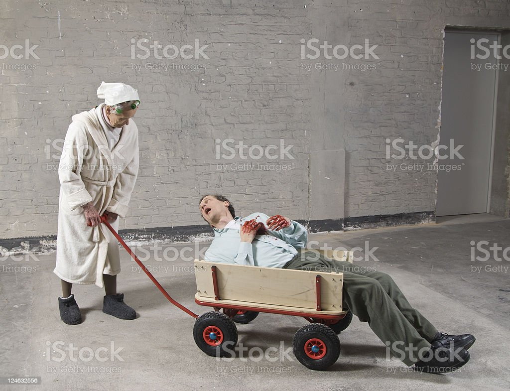 Old women in dressing gown pushing dieing man with cart stock photo