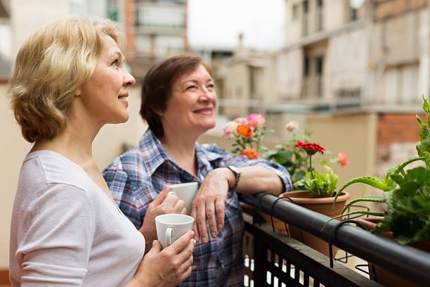 alte frauen auf dem balkon mit kaffee - nachbar stock-fotos und bilder