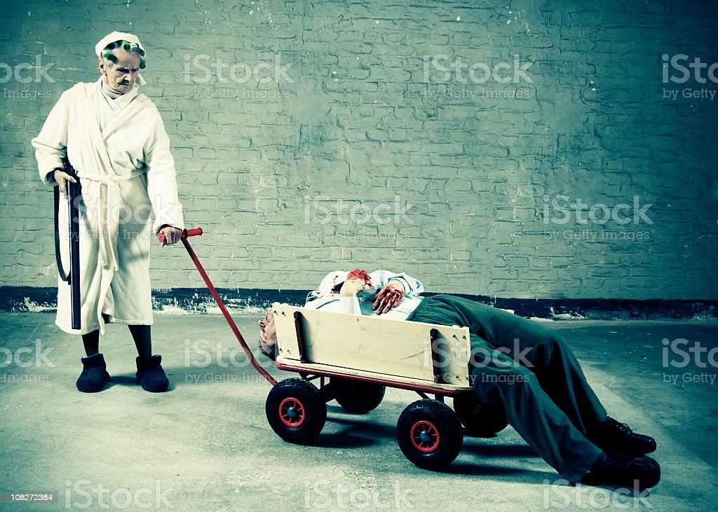 Old women pushing cart with dead man and shotgun stock photo