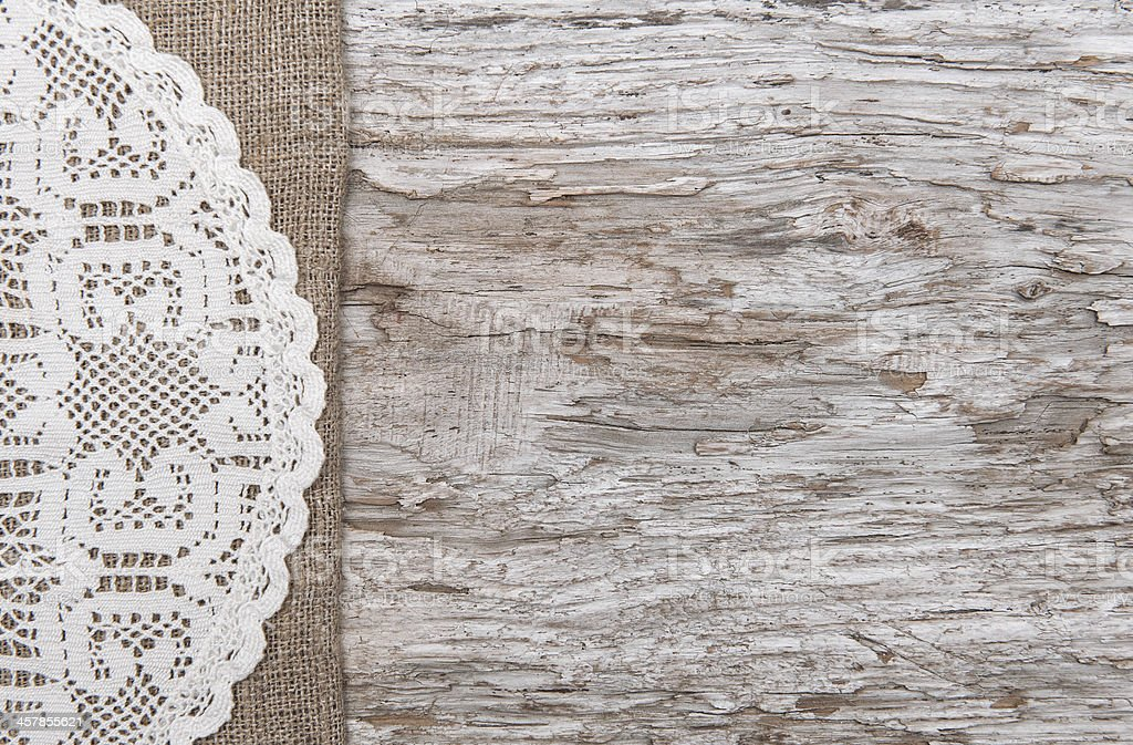 Old wood bordered by burlap and lacy cloth stock photo
