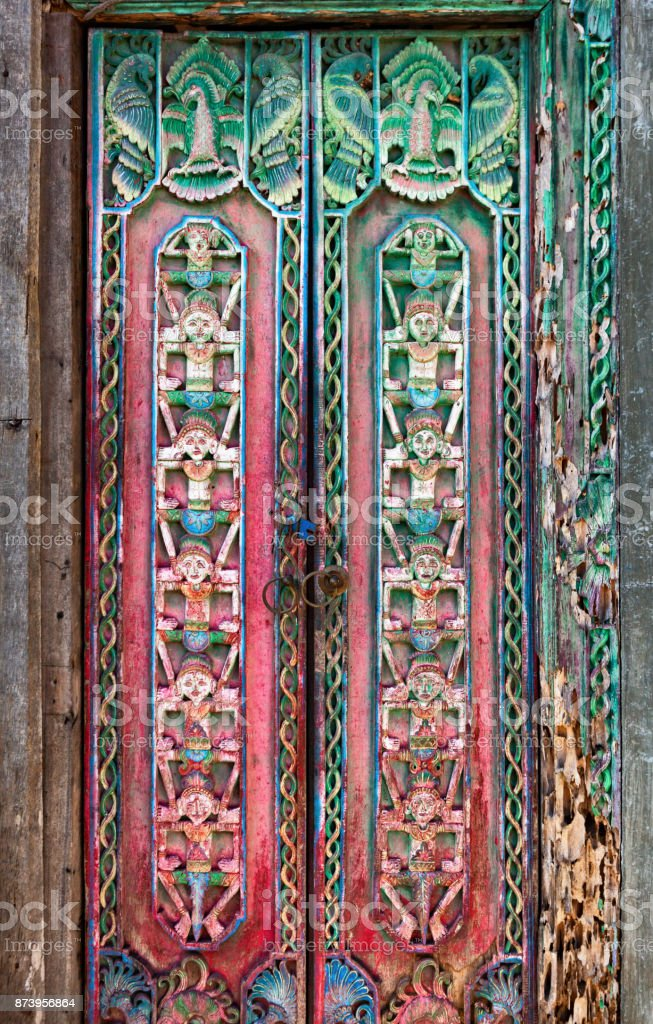 Old wood door with traditional Indonesian carving stock photo