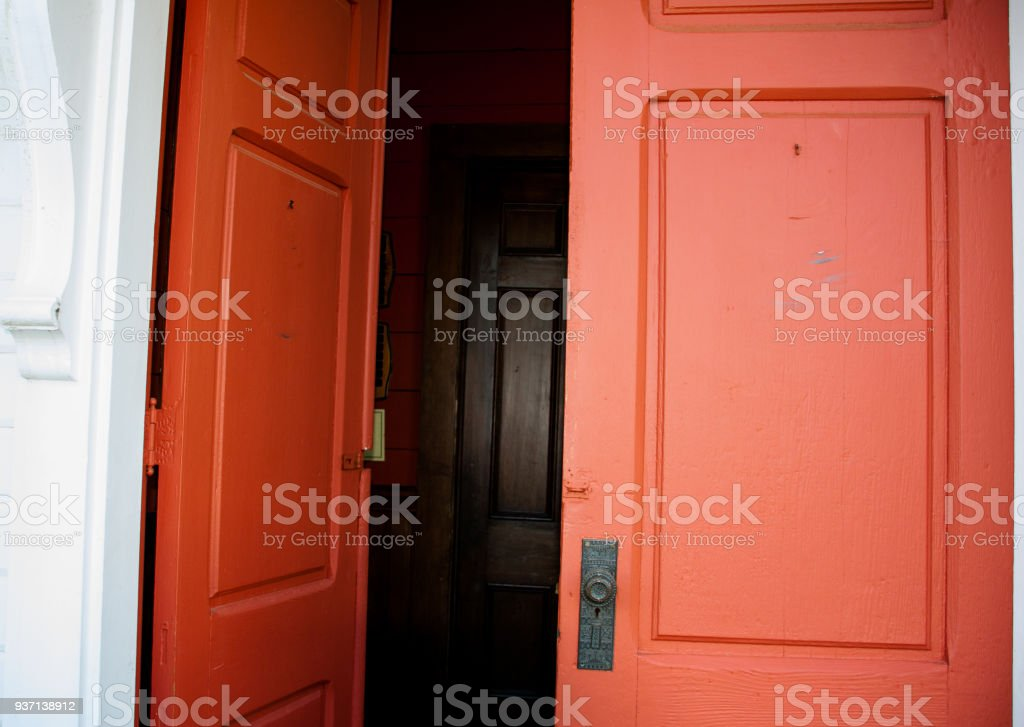 Old wood red double doors leading in to a dark hall with another set of doors visible inside stock photo