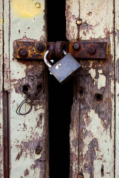 Old wood rural door with rusty padlock stock photo