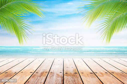 istock old wood table top on blurred beach background. 673475612