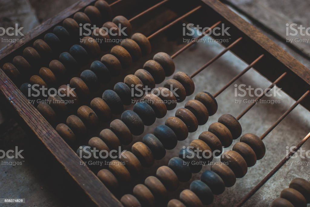 Old wooden abacus laying on dusty floor of storage. stock photo