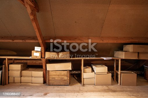 Old wooden attic interior with old cardboard boxes for storage or moving, close-up