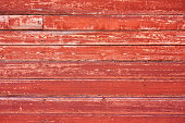 Old wooden background painted with red paint with a texture of cracks and scratches.