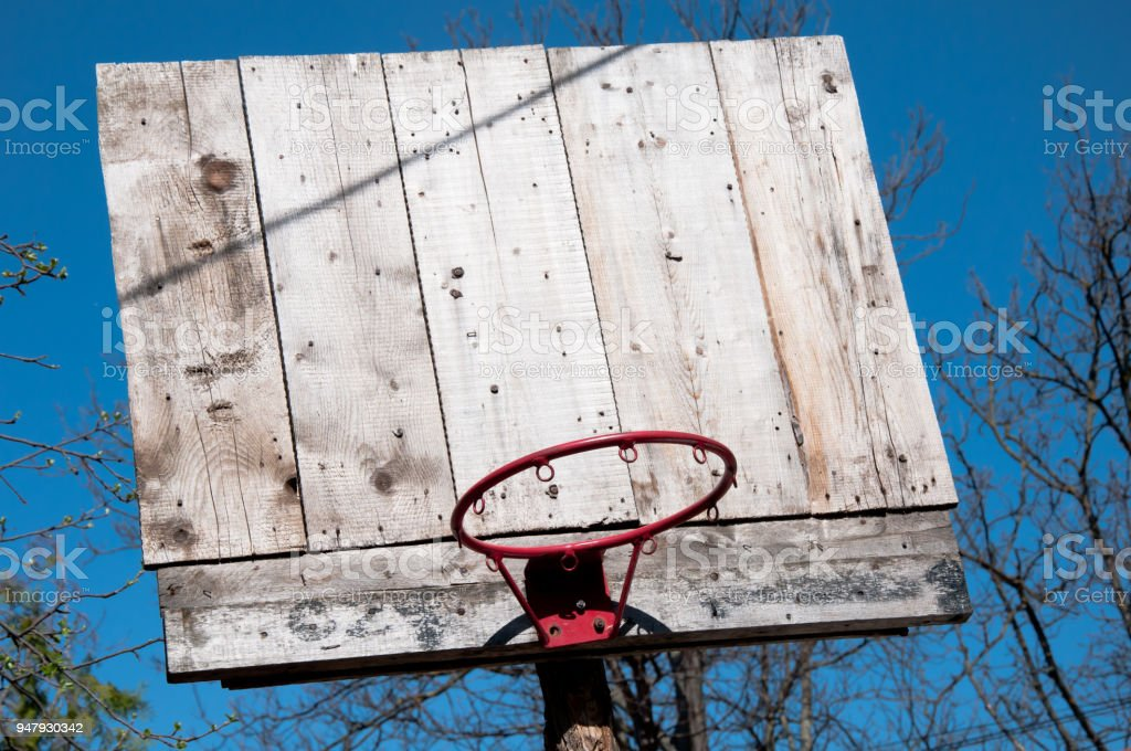 old wooden basketball board with red hoop without net