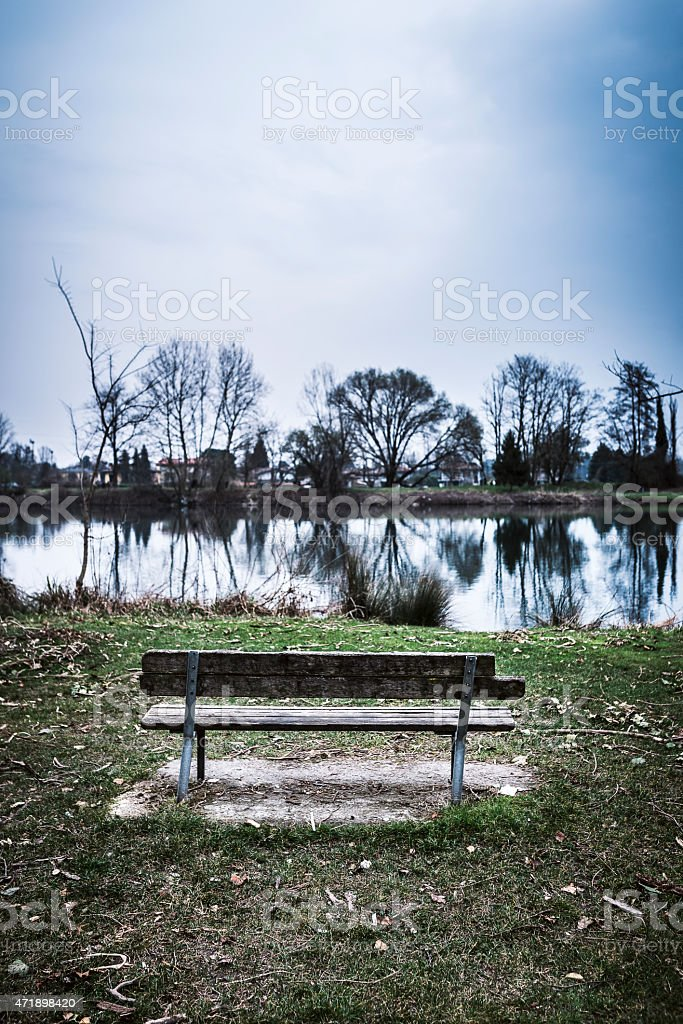 old wooden bench in front of a river stock photo