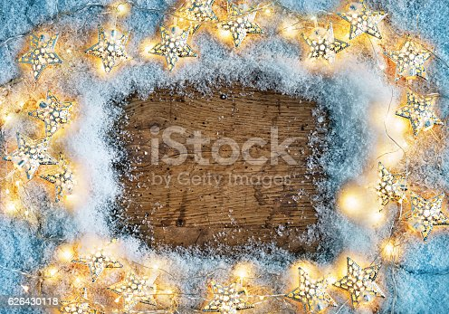 636659848 istock photo Old wooden board with snowflakes  and garland. 626430118