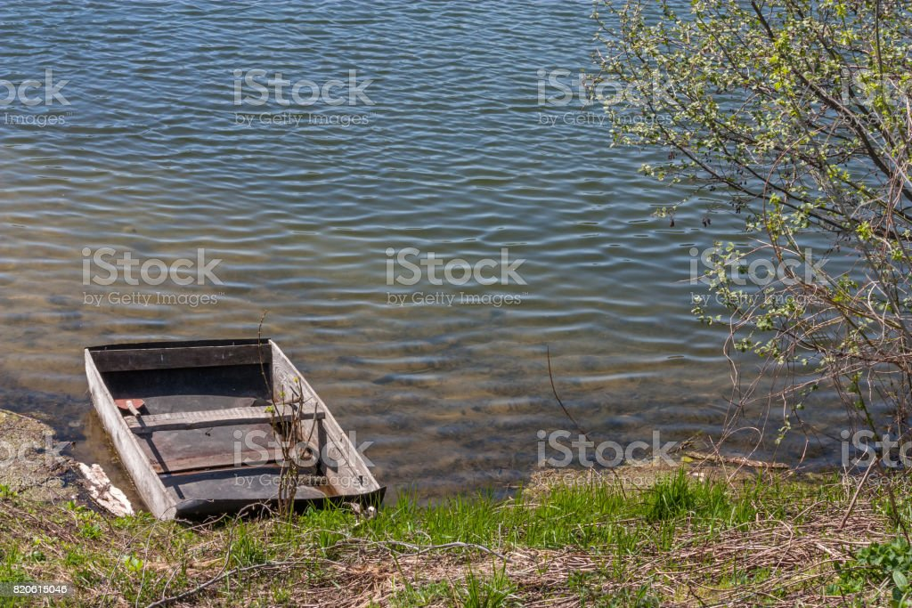 Old wooden boat moored to the bank of the lake stock photo
